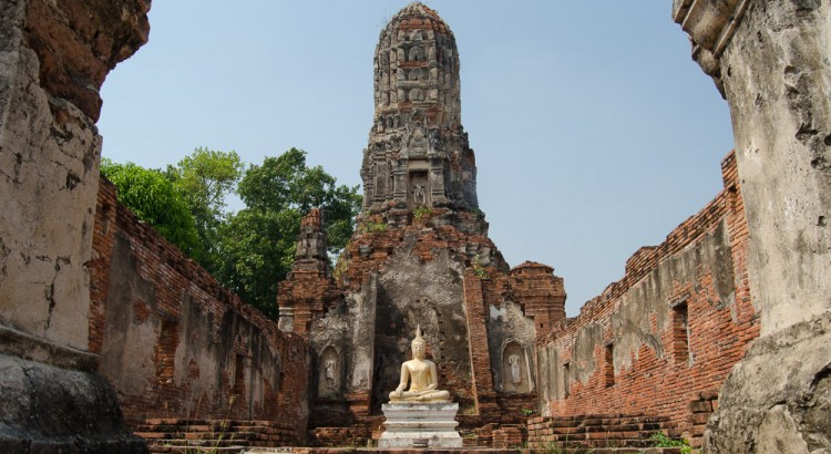 A golden Buddha statue in the ancient temple Wat Choeng Tha. The temple is in ruins, it has no ceiling.