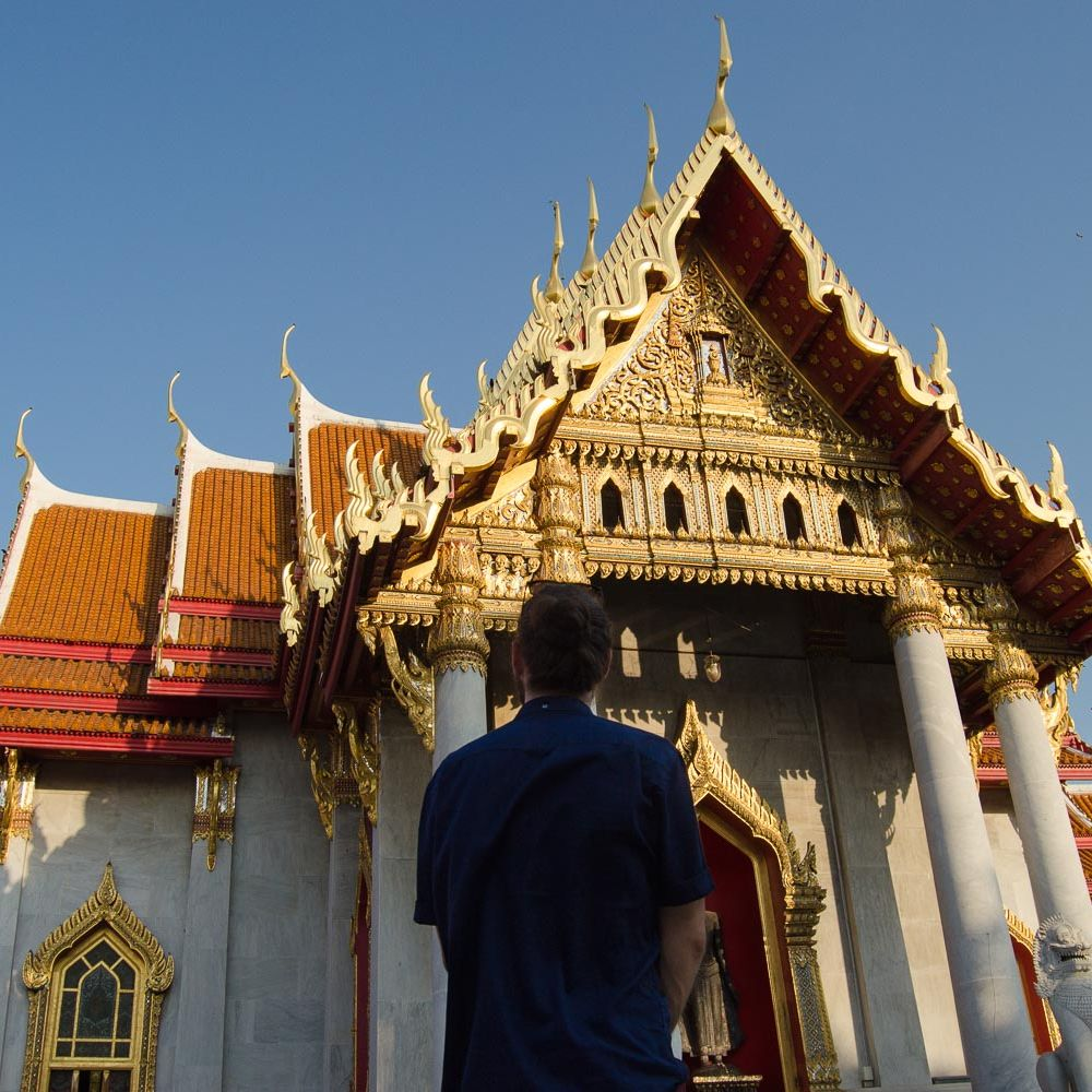 Introvert man alone staring at the Marble Temple in Bangkok