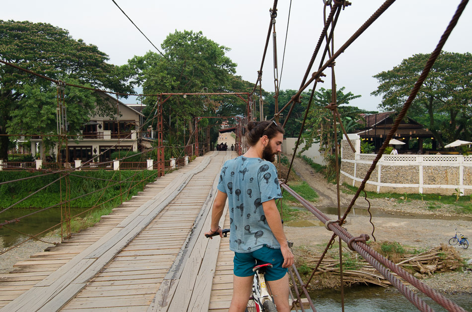 crossing a bridge in Vang Vieng